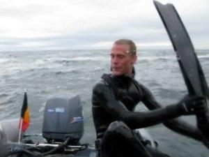 Undervandsjæger med svømmefødder i hænderne på en båd i Bretagne. Undervandsjagt.